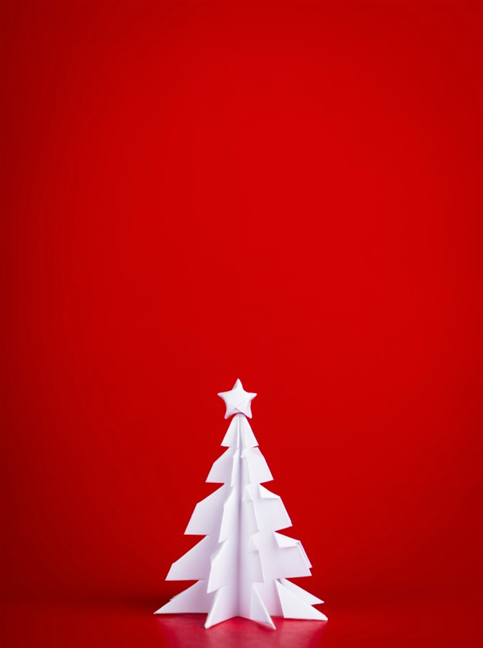 Simple Christmas tree made of paper, on a red background