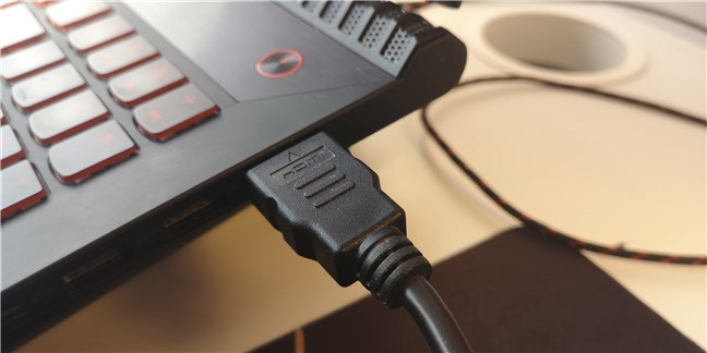 An HDMI cable connected to the HDMI port on a laptop