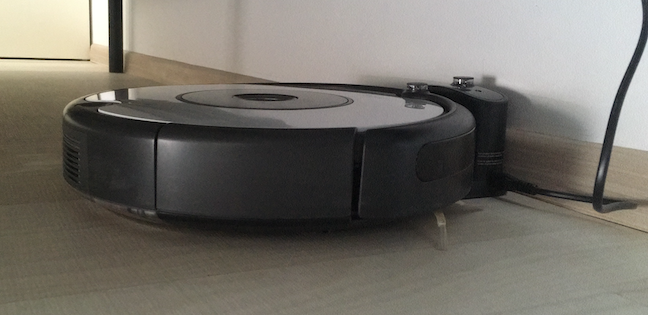 The Roomba docked safely in its Home Base under the bed